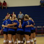 a photo of the volleyball team in a huddle in Hawaii