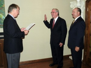 "William ""Steve"" Keith, center, gets sworn in to his position on the SAU Board of Trustees by Columbia County District Court Judge Mike Epley as Ark. Sen. Bruce Maloch looks on."