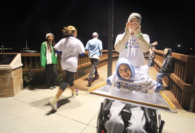 Hayden Cain Minor, 9 of Camden, and his stepfather, Paul Pharr, cheer on runners