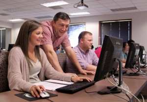 Ronnie Watson, assistant professor of management, helps student Sarah Clayton in SAU's first SAP ERP course offered this spring.